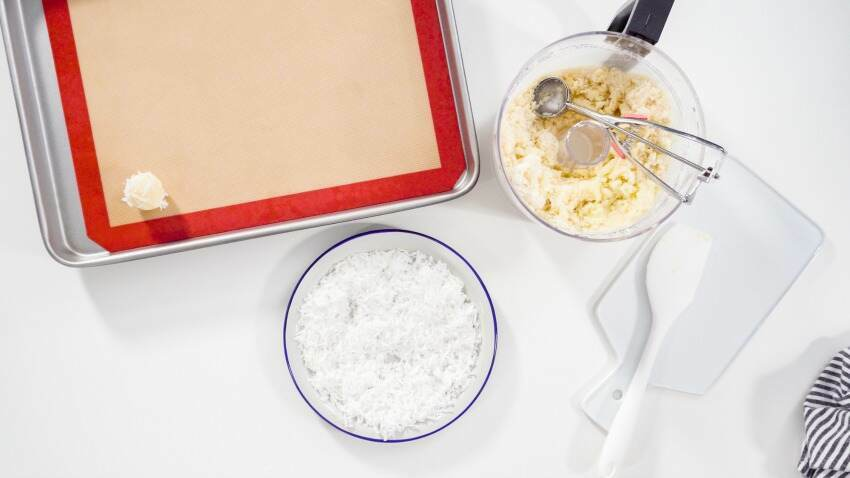 Flat lay. Scooping cookie dough into the baking sheet to bake coconut cookies.